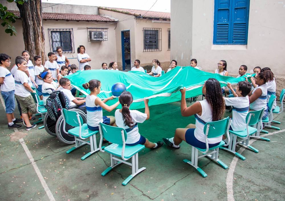 Em pátio escolar, estudantes seguram extremidades do tecido que simula um campo de futebol