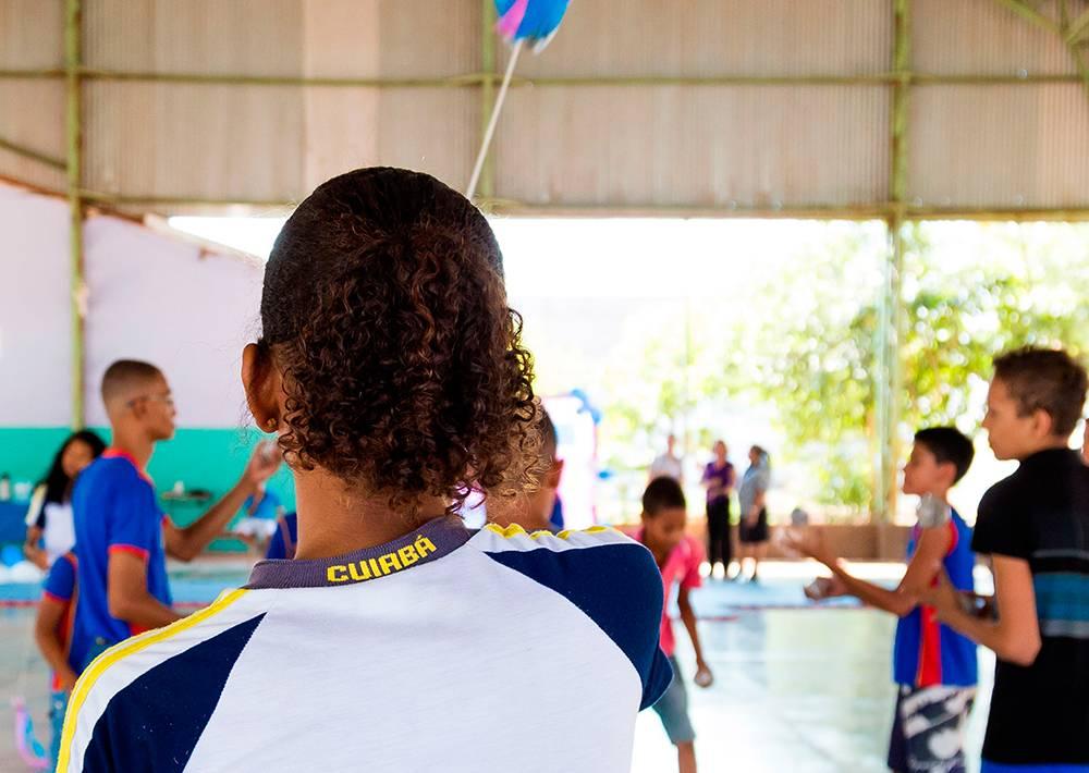 Menina com o uniforme escrito Cuiabá brinca com amigos em quadra escolar.