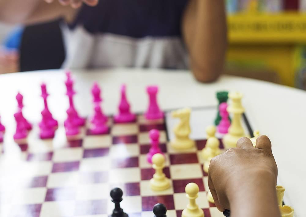Criança movimenta peça de xadrez e enquanto colega aguarda sua jogada