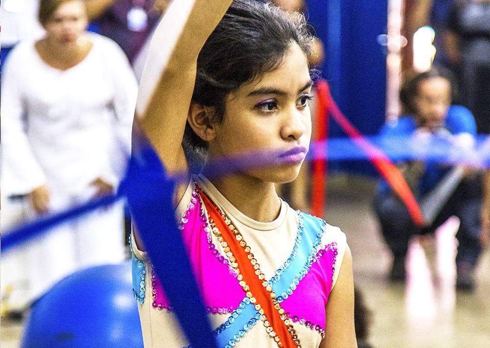 Menina com vestido bordado de lantejoulas movimenta fita de cetim
