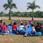 Grupo de pessoas com e sem deficiência estão reunidos em círculo sobre uma lona azul, em cima da grama. Eles conversam entre si. Está um dia ensolarado no parque e há coqueiros e árvores ao fundo.