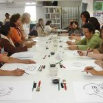 Turma de mulheres sentadas em torno de comprida mesa branca desenham retratos em grafite sobre folhas brancas. À frente de cada papel, estão pincel, lápis e potes de água dispostos. Elas riem enquanto observam os desenhos.