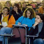 Grupo de mulheres sentadas em auditório em cadeiras universitárias prestam atenção em aula. Algumas delas fazem anotações.