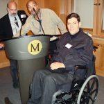 Rodrigo posa ao lado de púlpito com selo com a letra M ao centro. Ele usa cadeira de rodas e está em uma sala com paredes de madeira e carpete. Ao fundo, dois homens ajustam apresentação no palanque.