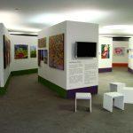 Sala ampla e vazia onde há painéis com exposição de quadros. No painel em destaque há uma televisão e texto descritivo do Programa Plural.