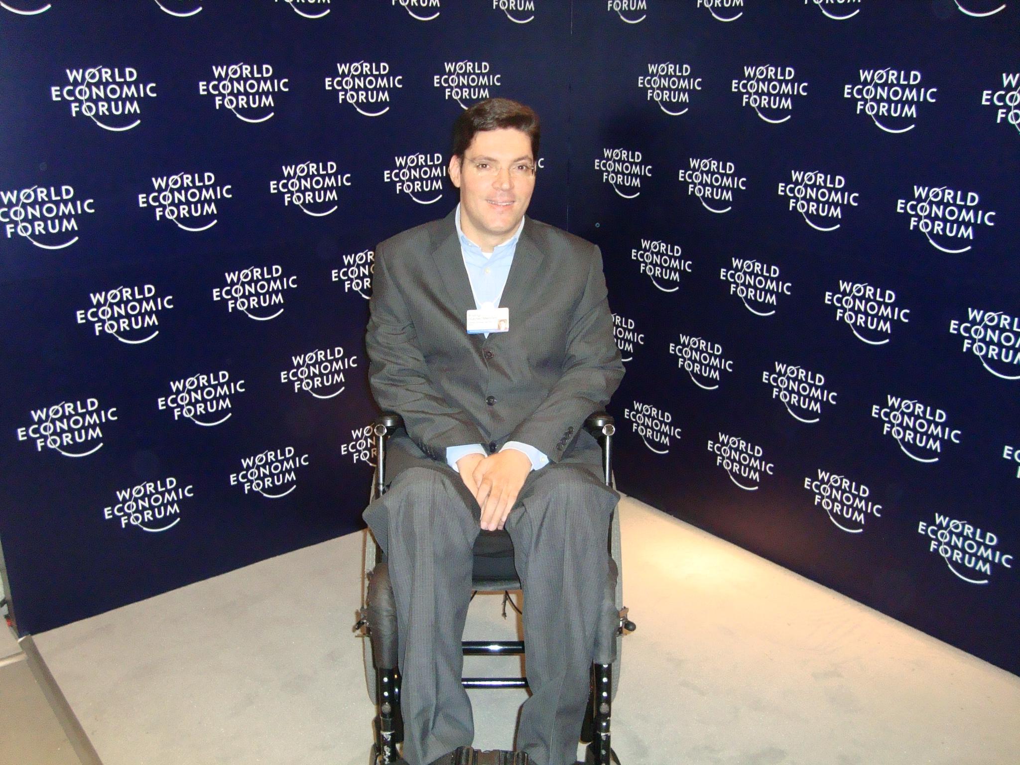 """Rodrigo posa para foto em sua cadeira de rodas, vestindo terno e camisa. Ao fundo, painel escuro estampado com inúmeros logotipos do """"Fórum Econômico Mundial""""."""