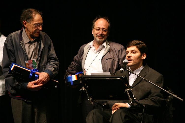 Dois homens em pé seguram presentes e olham com admiração para Rodrigo, enquanto ele fala ao microfone sentado em sua cadeira de rodas.