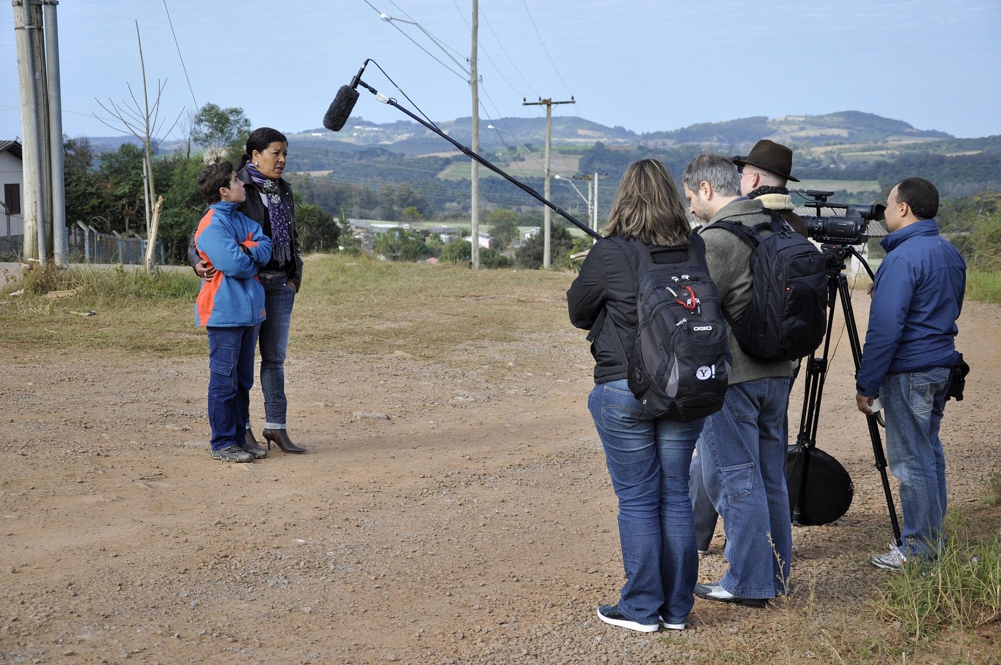 A céu aberto, em estrada de terra, equipe de gravação com câmera, microfone e mochilas está posicionada em pé e de costas, no canto direito da foto. Ao lado esquerdo da imagem, posicionados à frente da equipe, mãe contorna seu braço nas costas de seu filho, que de braços cruzados a observa.