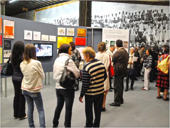 Grupo de pessoas visita exposição de obras de arte em sala ampla com painéis cinza. Ao fundo, parede estampada com foto ampliada de pessoas que posam enfileiradas.