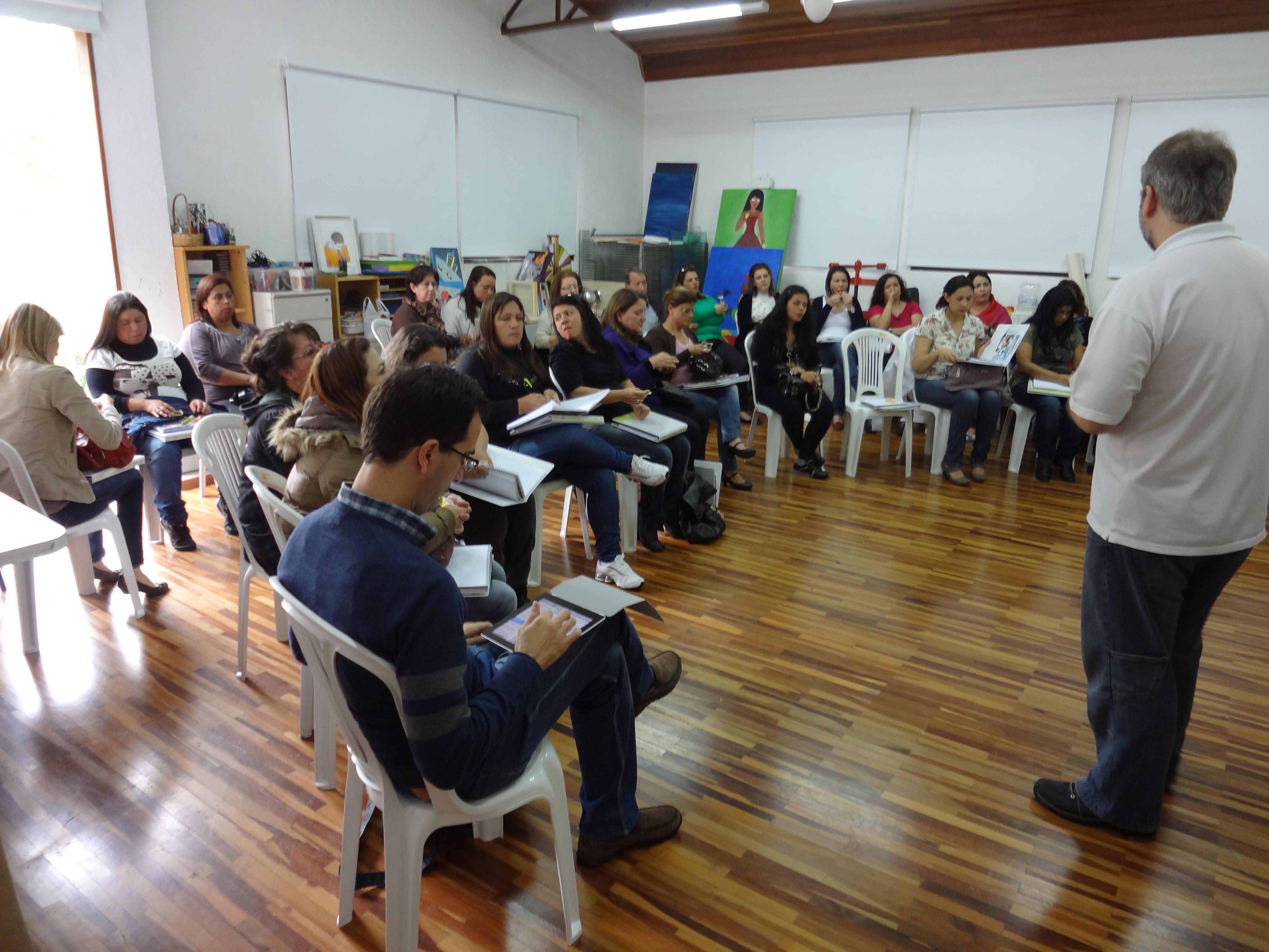Grupo de pessoas sentadas em cadeiras plásticas que formam um semicírculo. Eles estão fazem anotações atentos ao palestrante que está em pé no centro da sala.