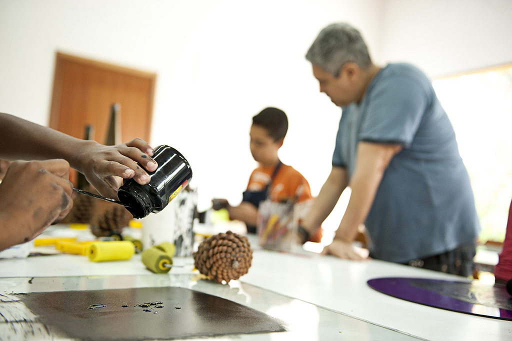 Ao lado esquerdo, em evidência, mão de jovem despeja tinta preta sobre a mesa. Nela, há uma pinha e rolos de espuma. Ao fundo, professor observa outro aluno trabalhando.