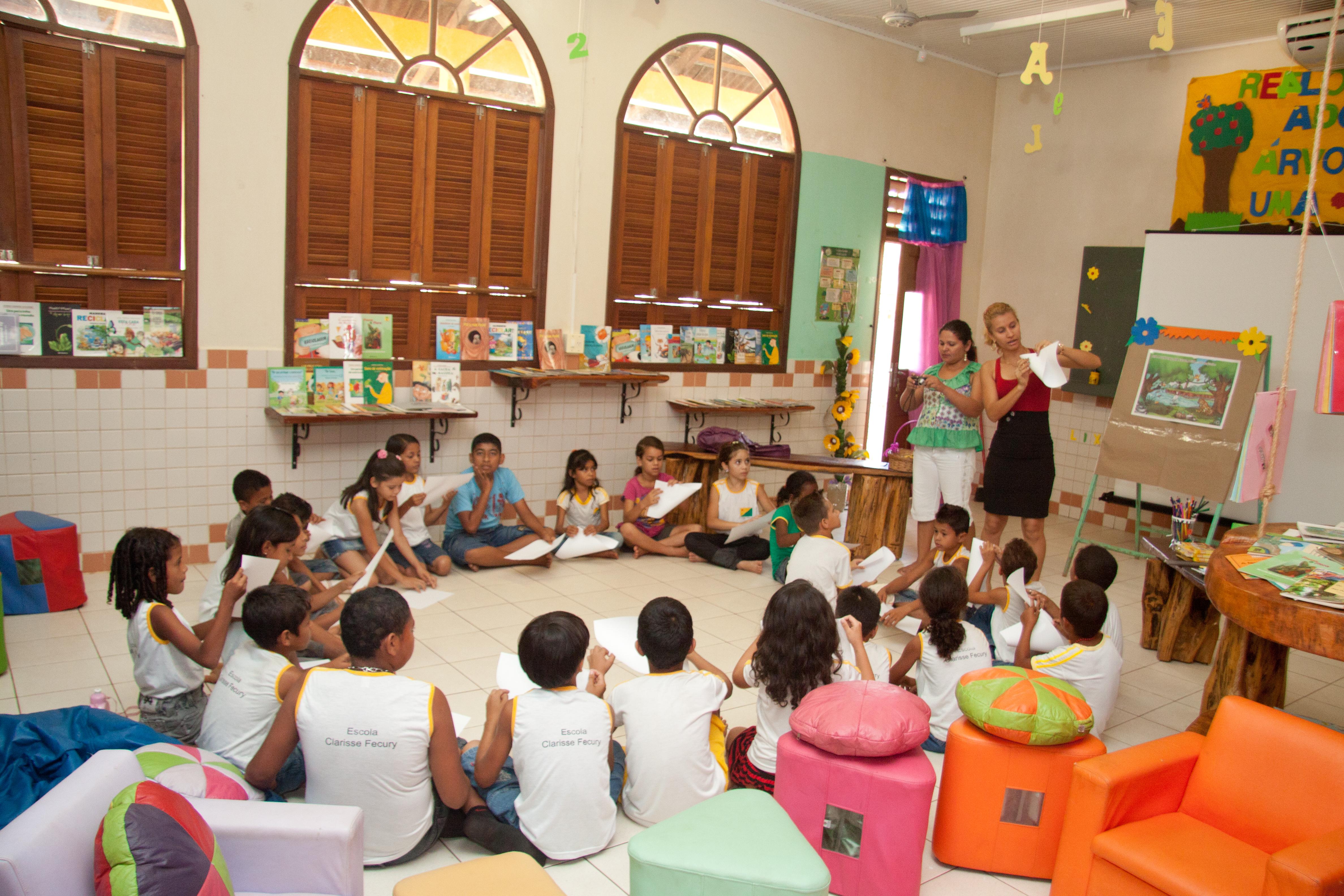 Em sala uma sala ampla com janelas grandes, crianças sentadas em roda no chão seguram folhas sulfites e observam a professora, que de pé, que faz uma dobradura. Nas paredes da classe há estantes de livros e no chão almofadas coloridas de diferentes tamanhos.