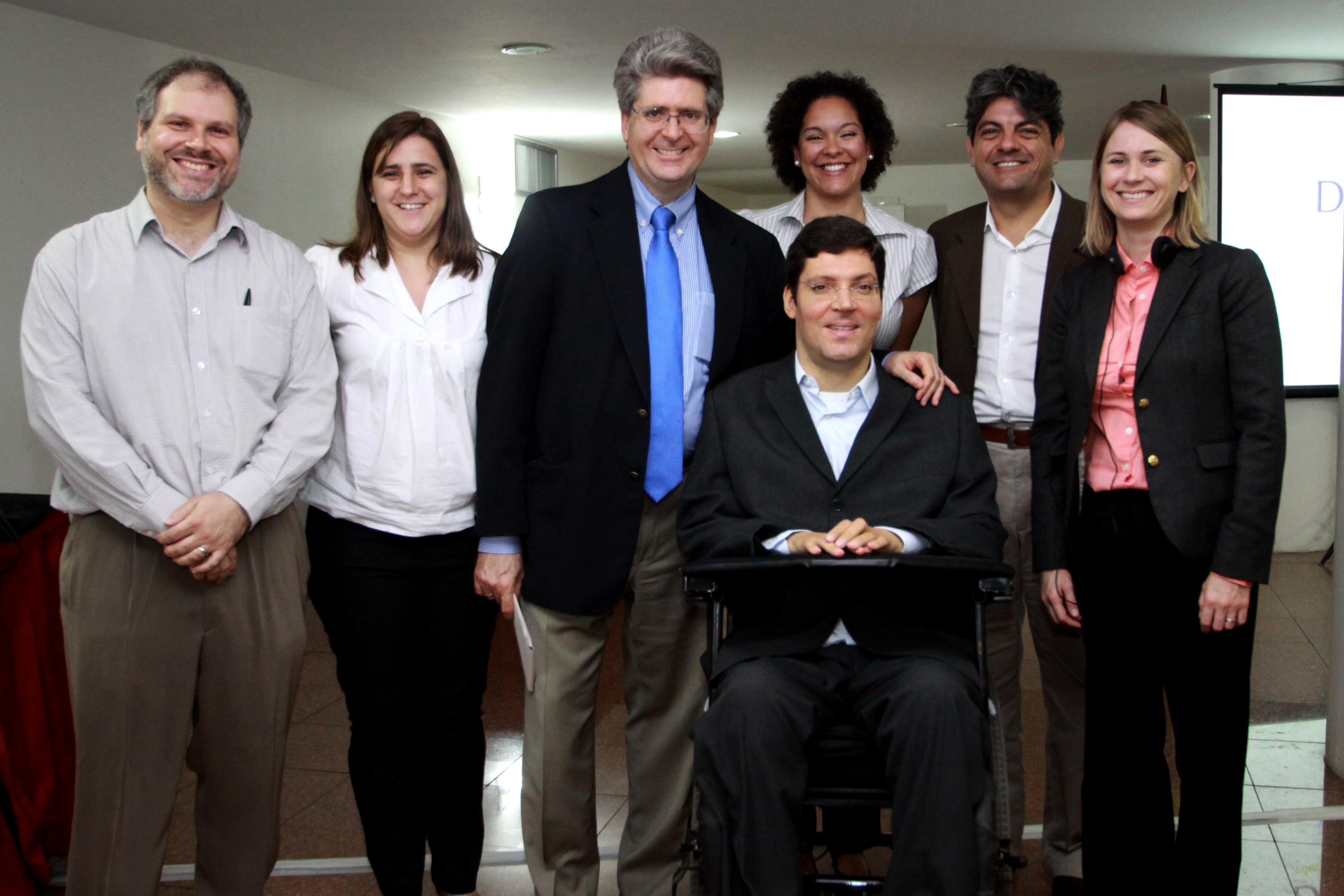 Grupo de homens e mulheres vestidas em traje social posam para foto em sala. Um deles apoia seu braço esquerdo no ombro de Rodrigo, que está ao centro em sua cadeira de rodas.