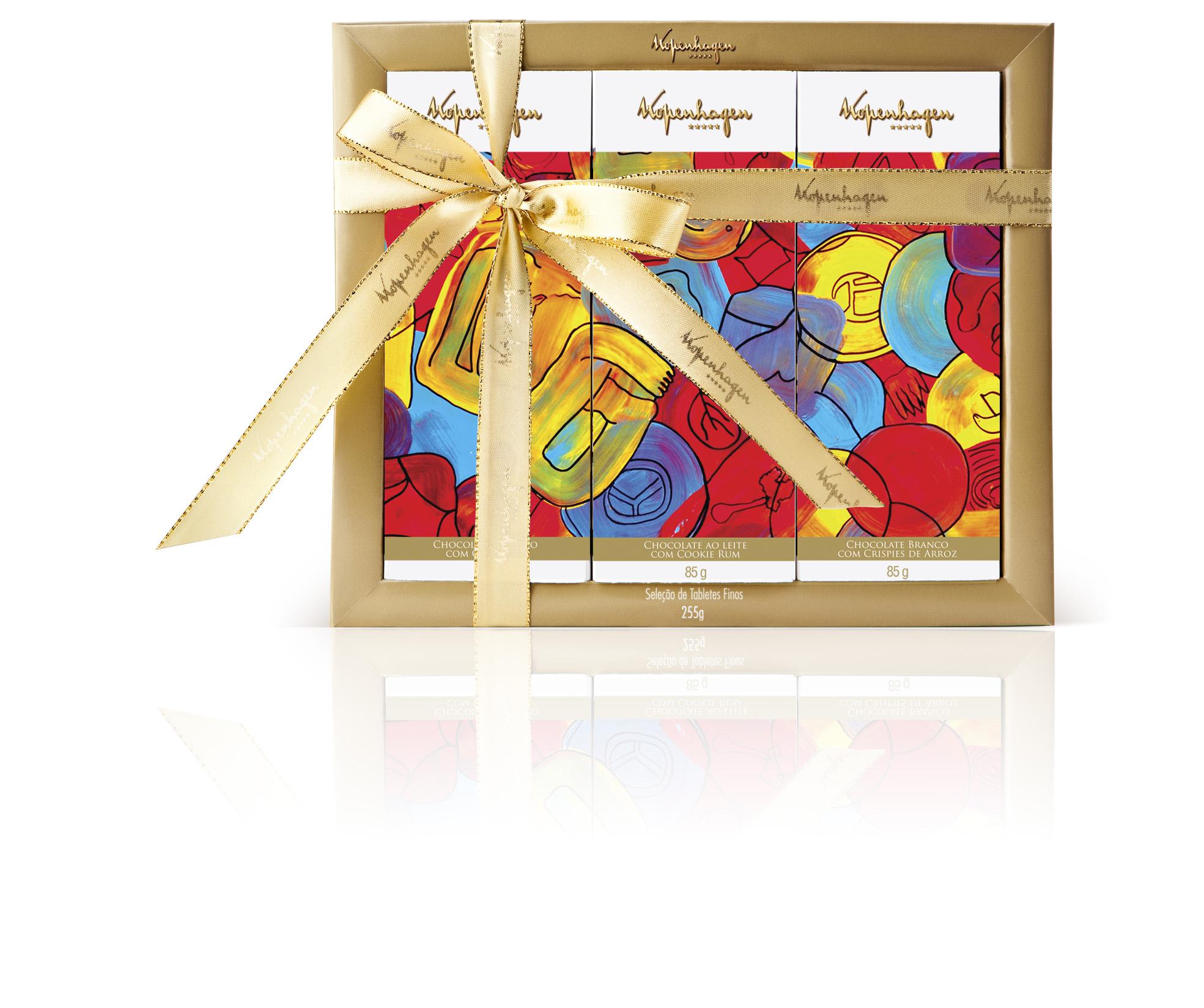 """Caixa de embalagem quadrada com borda dourada e a inscrição """"Kopenhagen"""" contendo três tabletes de chocolate em embalagens estampadas com obra de arte abstrata e colorida. A caixa está envolta por fita dourada e um grande laço."""
