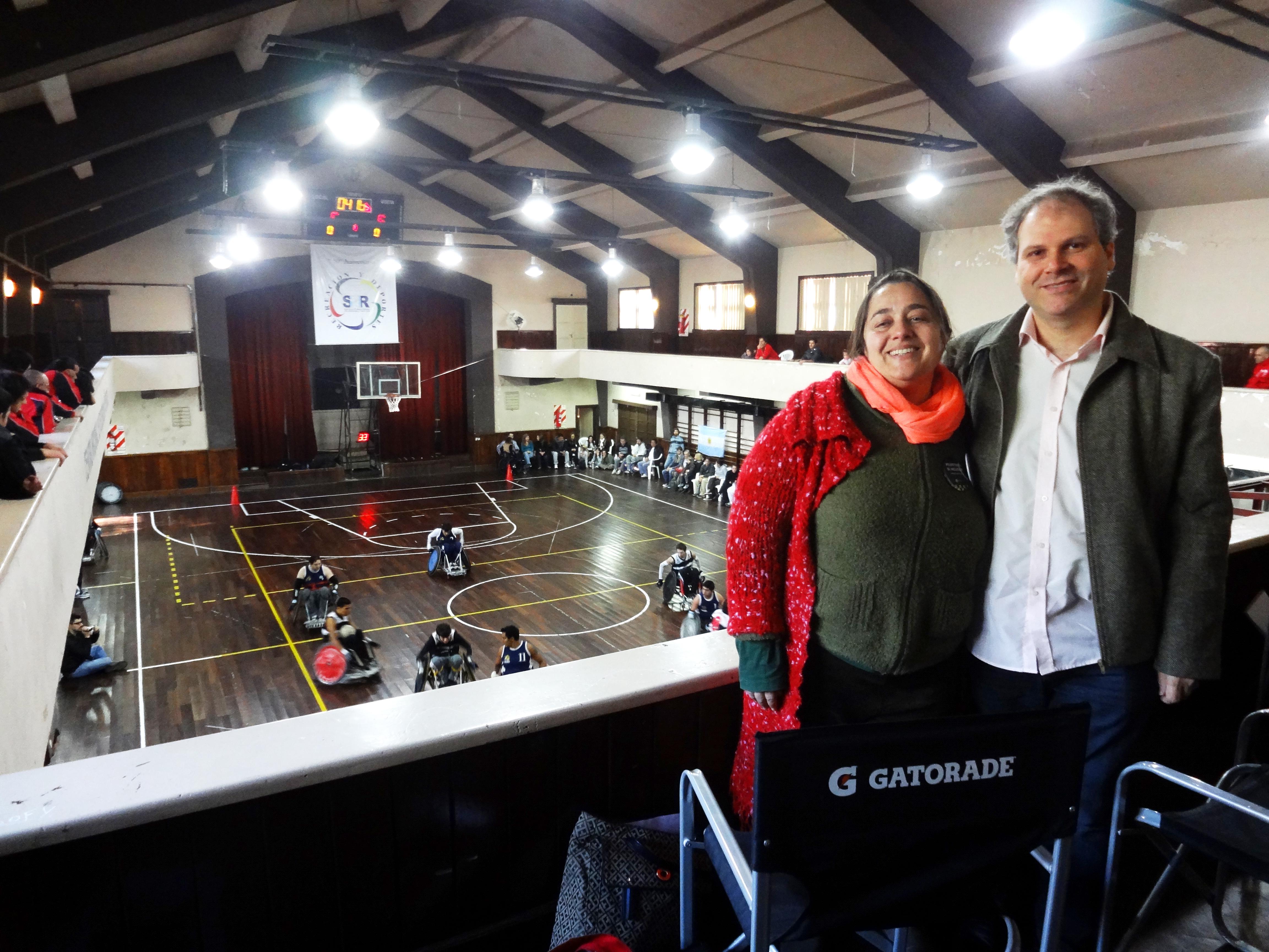 Homem e mulher posam para foto, em pé, no canto esquerdo da imagem. Eles estão na parte superior de um ginásio. Na quadra, de piso de madeira, atletas jogam basquete em suas cadeiras de rodas.