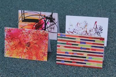 Quatro cartões estampados com obras de arte abstratas e coloridas posicionados em forma triangular sobre fundo verde.