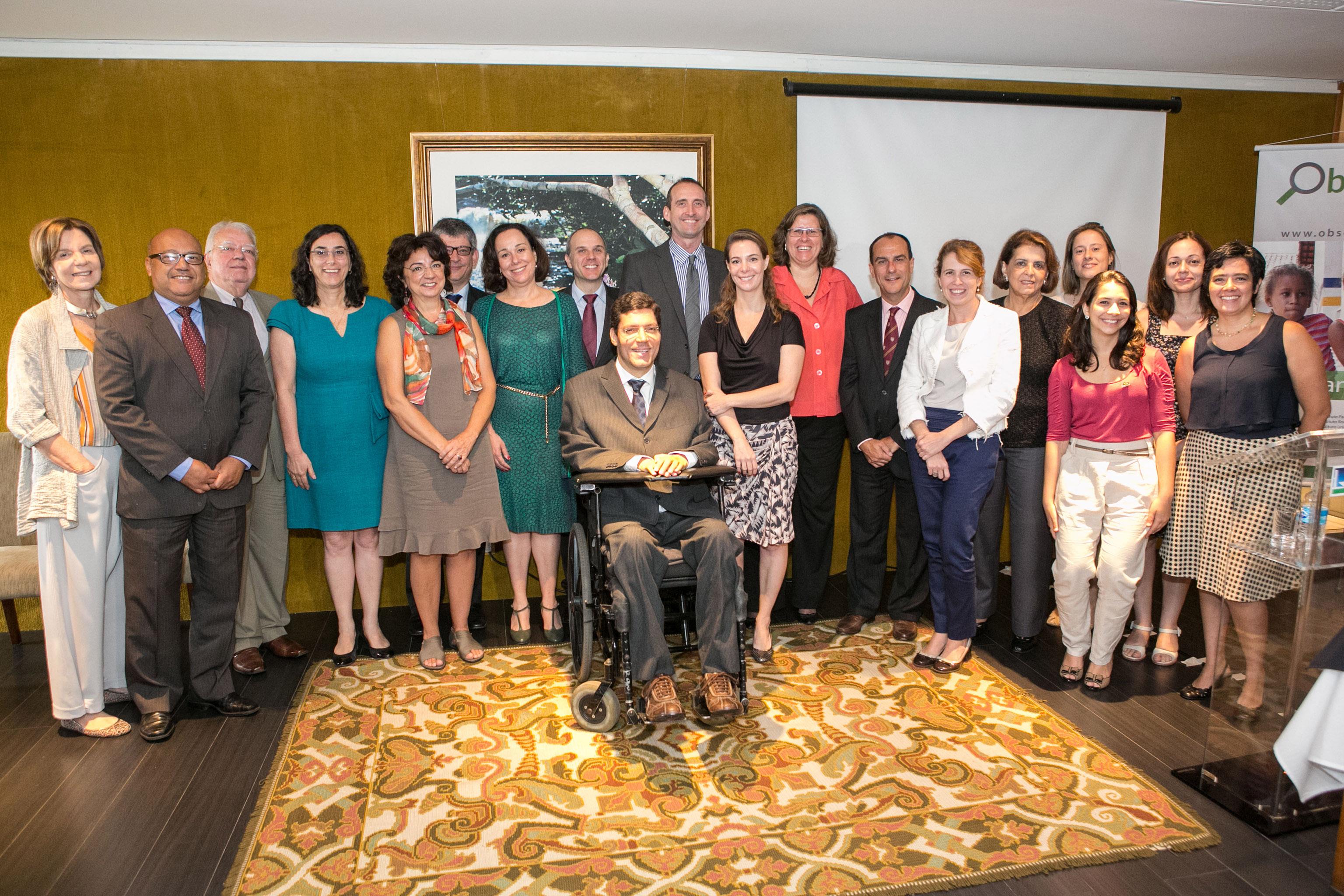 Mulheres e homens em trajes sociais posam para a foto. Elas estão sorridentes e enfileiradas lado a lado, ao centro, Rodrigo em sua cadeira de rodas. No chão, grande tapete estampado.