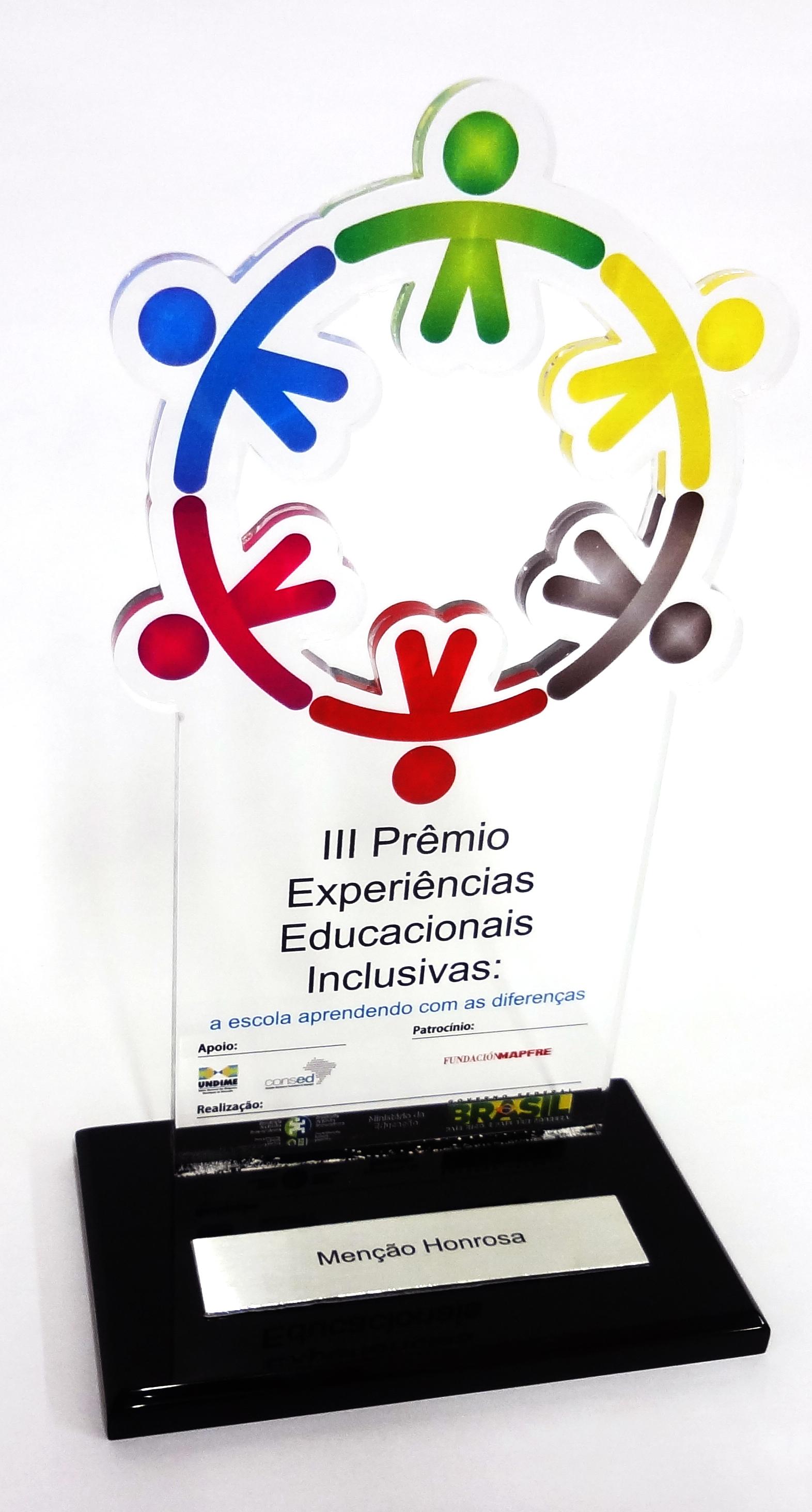 """Troféu do prêmio em acrílico, com símbolos coloridos de pessoas de mãos dadas formando um círculo. Em sua base, uma placa com a descrição """"Menção Honrosa""""."""