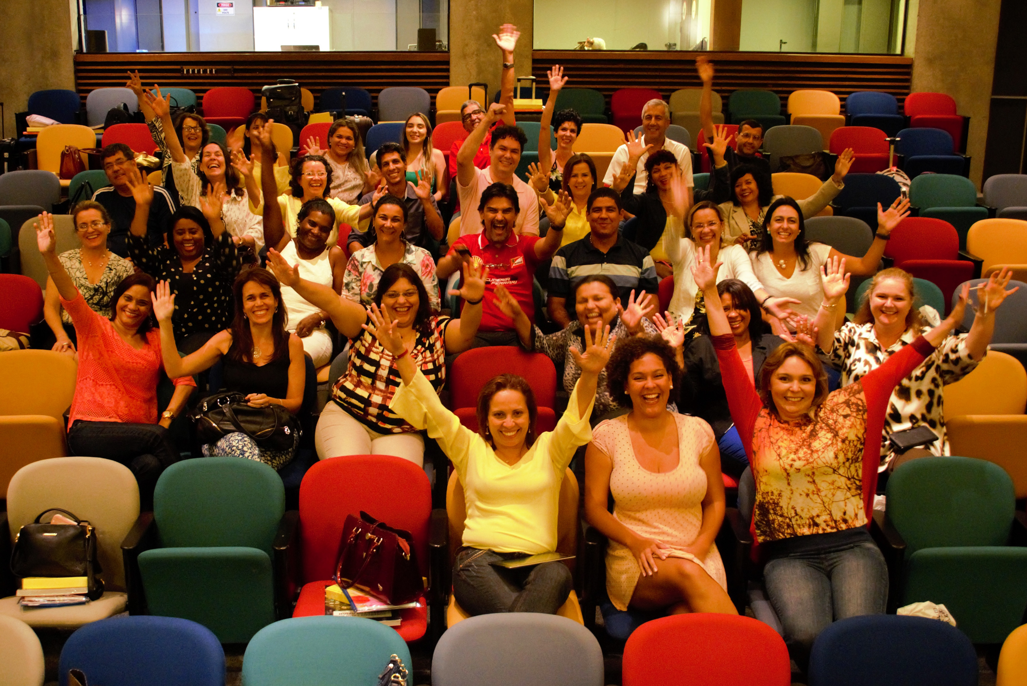: Homens e mulheres animados e com os braços erguidos posam para foto em auditório com cadeiras coloridas.