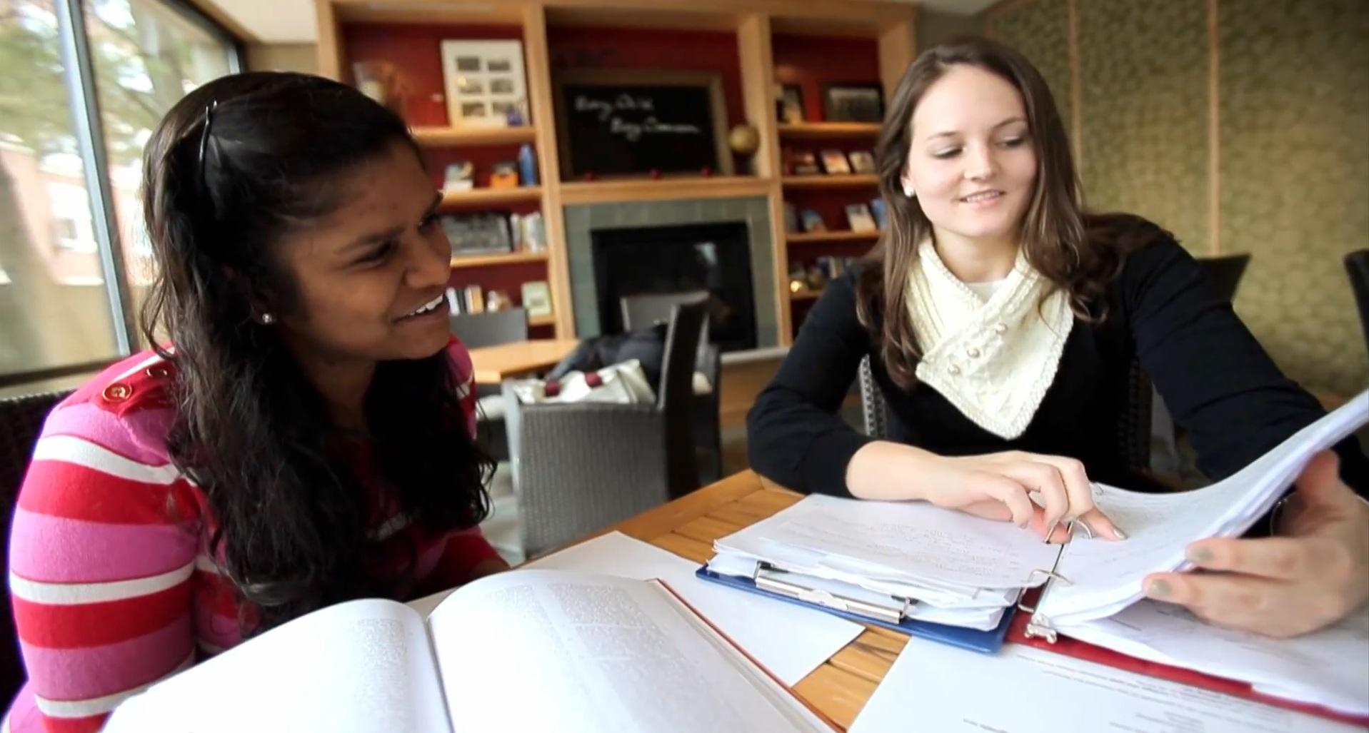 Duas jovens estão em uma sala de leitura. Ao lado esquerdo, uma delas aponta para as anotações de seu fichário, enquanto a que está ao lado esquerdo, olha sorridente.