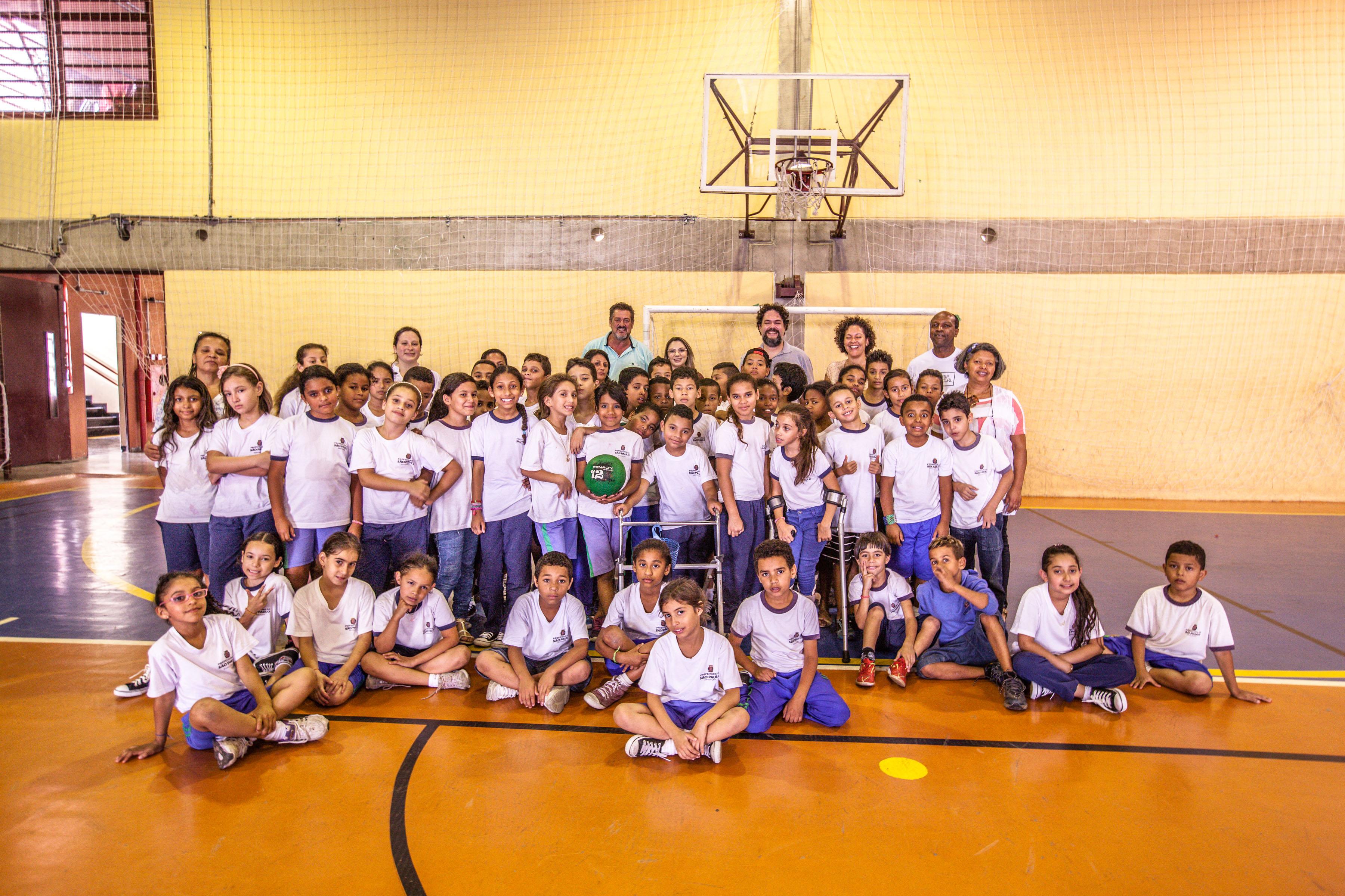 Em quadra poliesportiva, crianças com e sem deficiência e educadores posam para foto. A maioria está enfileirada em pé ao fundo, enquanto outras crianças estão sentadas no chão e em frente ao grupo.