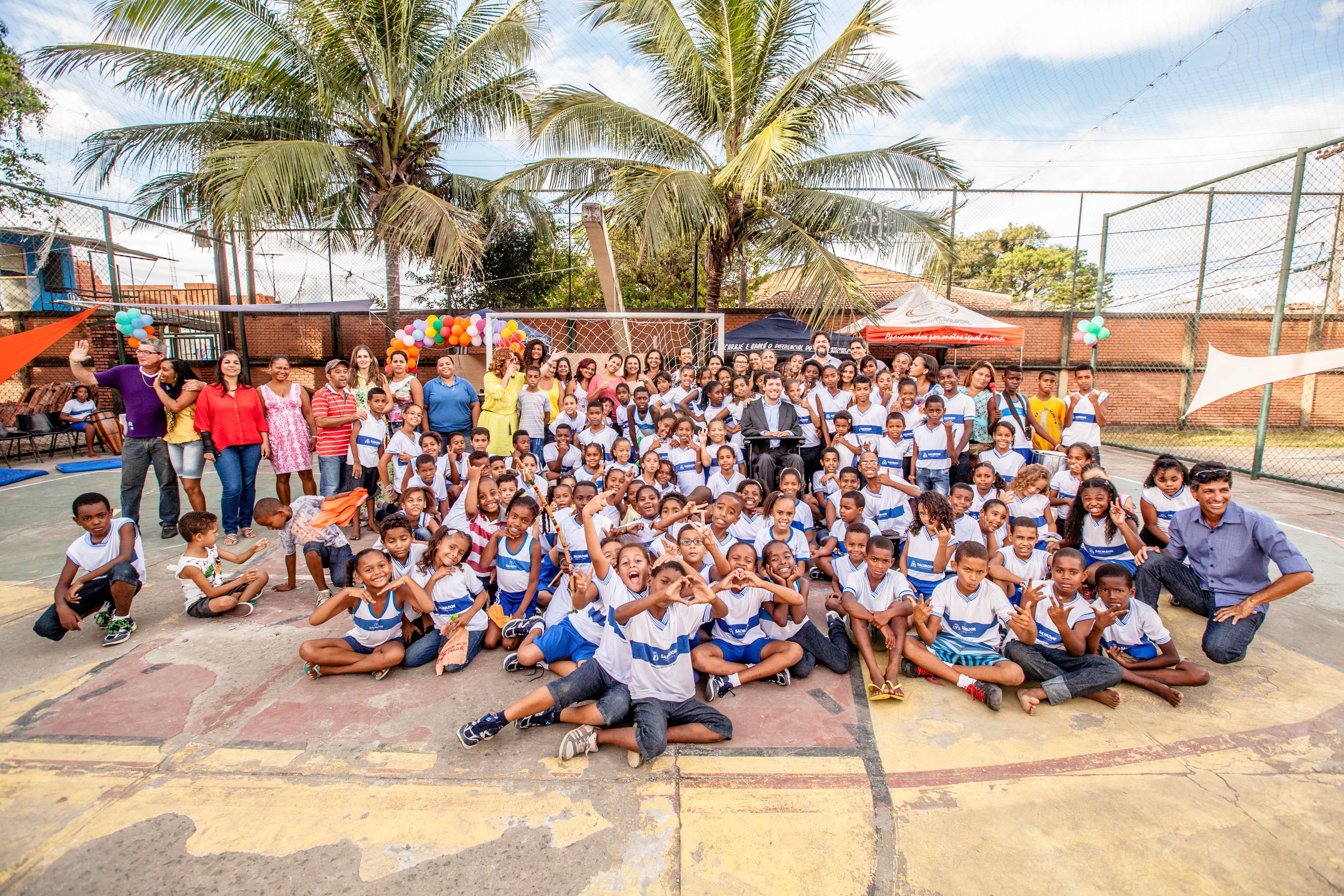 Grande grupo de crianças e educadores posam sorridentes para foto junto a Rodrigo, que está ao centro. Muitos estão sentados no chão em frente ao que estão enfileirados em pé. Eles estão em uma quadra poliesportiva, o dia está ensolarado e ao fundo há coqueiros e balões coloridos.