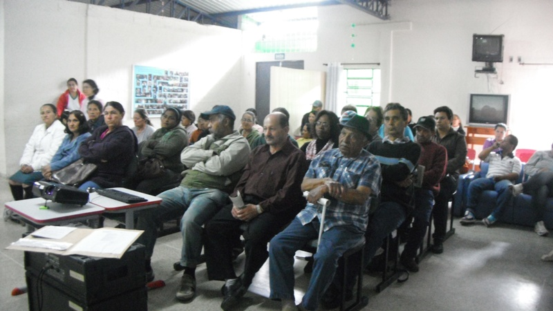 Homens e mulheres sentados enfileirados em sala branca.