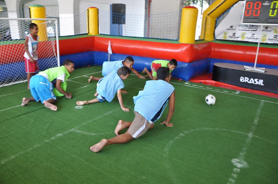 Garotos engatinham e movimentam-se atrás de bola sobre tapete com marcações de campo de futebol. Ao fundo, um deles está rindo, em pé, no gol. Os demais usam coletes azuis ou verdes.