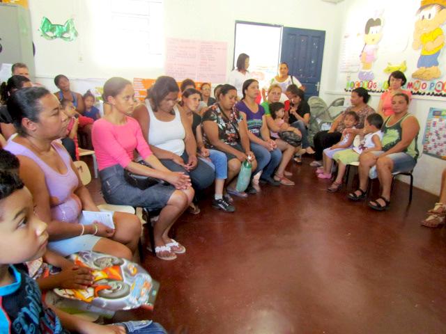 Em sala de aula, mulheres formam semicírculo sentadas em pequenas cadeiras. Algumas estão com crianças em seu colo.