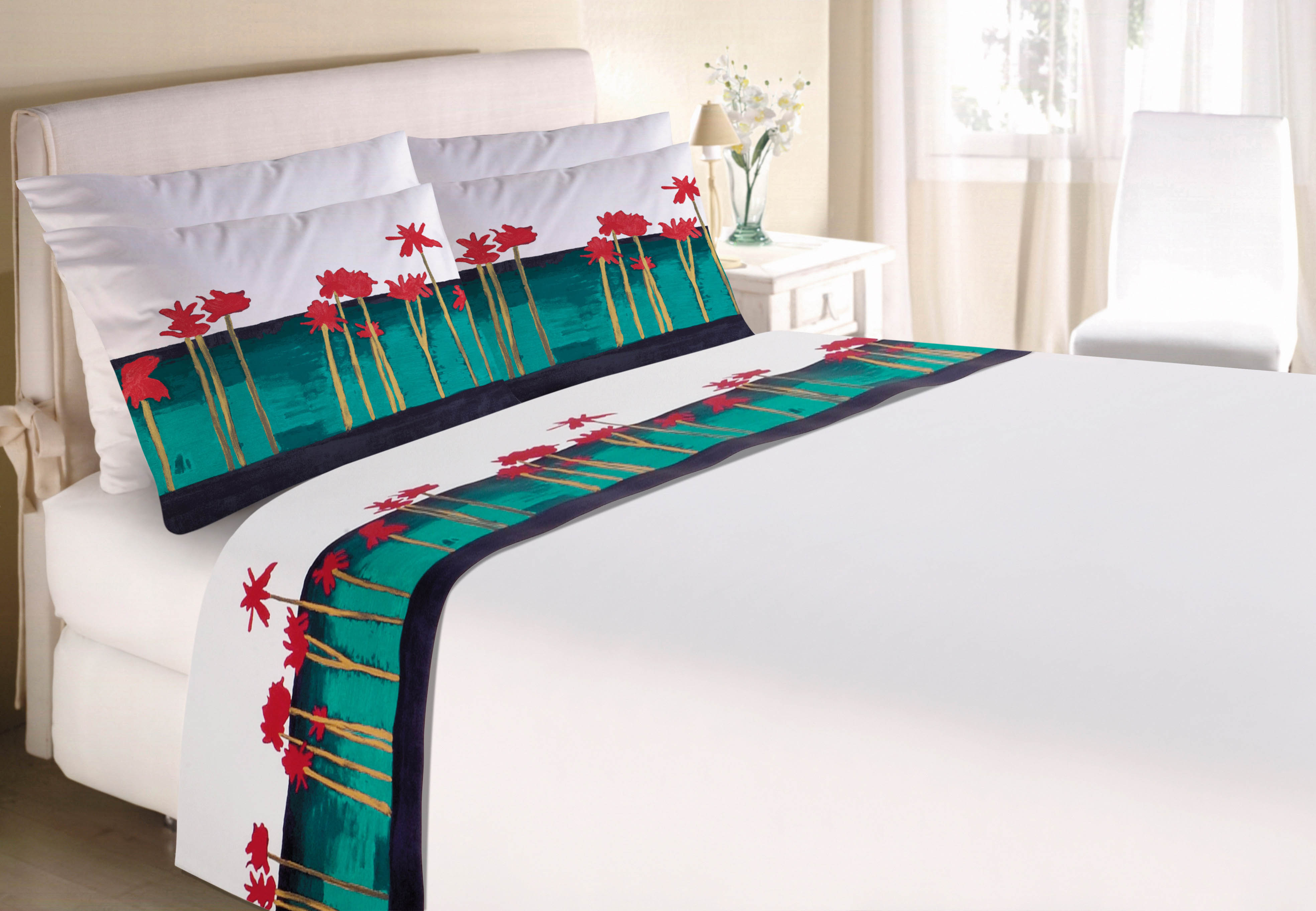 Em destaque cama de casal com jogo de lençóis e fronhas brancos estampados com obra de arte com flores vermelhas e fundo verde-água. Ao fundo, quarto mobiliado em branco.