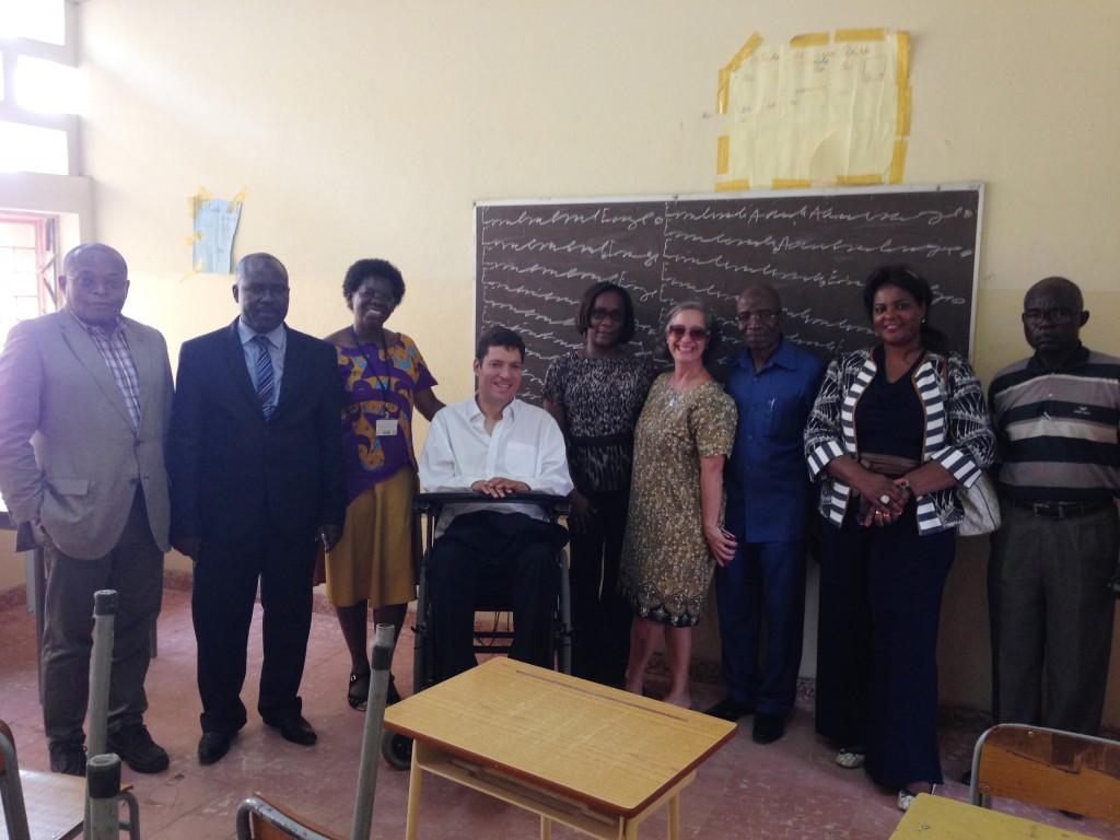 Em pé, homens e mulheres posam sorridentes em uma sala de aula. Ao centro está um homem em cadeira de rodas. Ao fundo, quadro negro escrito com giz branco e 2 cartazes colados com fita adesiva acima e ao lado esquerdo da lousa.