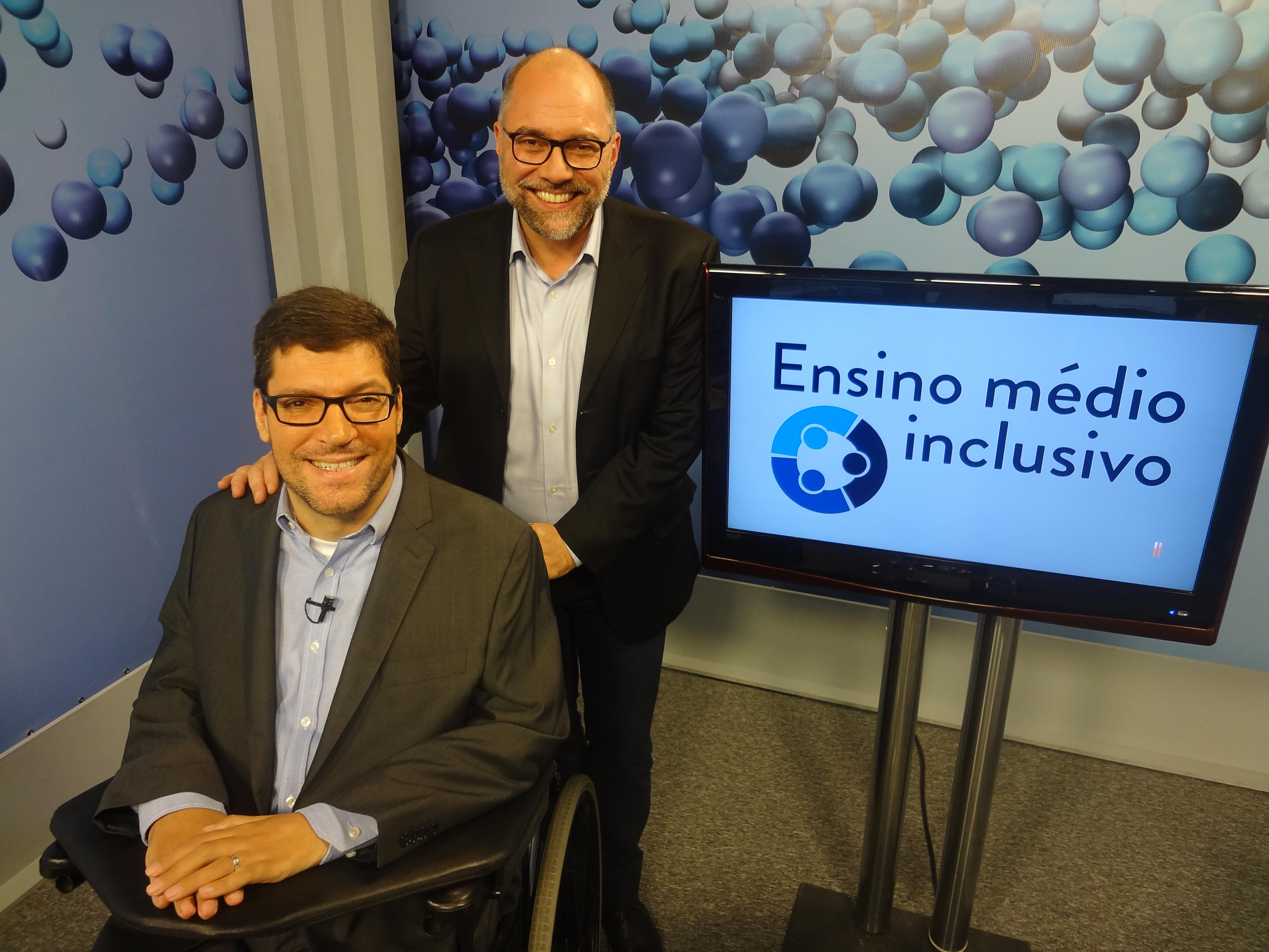Rodrigo Hübner Mendes e Ricardo Henriques sorriem, ao lado televisão com o logo do Ensino médio inclusivo