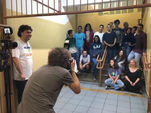 Fotógrafo, de costas, registra alunos e professores na escada da escola. Homem alto, ao lado, o observa sorrindo.