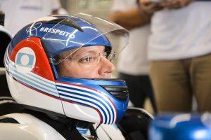 Rodrigo Hübner Mendes aparece já dentro do carro de corrida com capacete e traje de proteção..