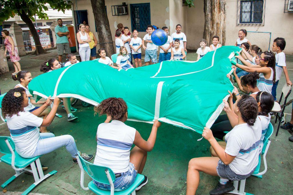 Em um pátio escolar, cerca de 15 alunos estão sentados em cadeiras, posicionadas de forma triangular em uma aula de educação física inclusiva. Os estudantes seguram com as duas mãos um grande pano verde, que simula um campo de futebol, incluindo as linhas de marcação. Eles sacodem o tecido para fazer uma bola azul, colocada sobre o pano, se movimentar.