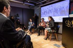Três mulheres estão sentadas diante de uma plateia. Uma delas fala ao telefone.