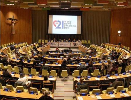Salão da ONU, com mesas e cadeiras. Na tela ao centro, o símbolo do Dia Internacional da Síndrome de Down.