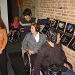 Pessoas com e sem deficiência visitam exposição de arte com recursos de acessibilidade. Visitantes com deficiência física utilizam fone para conferir audiodescrição das obras expostas em parede de tijolo.