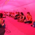 Dentro de um túnel de tecido vermelho há duas fileiras de mulheres sentadas lado a lado. Na ponta esquerda, uma delas segura o microfone.