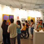 Pessoas com e sem deficiência visitam exposição de arte dentro de uma sala branca. Elas observam atentamente quadros e esculturas, destacadas por focos de luz.