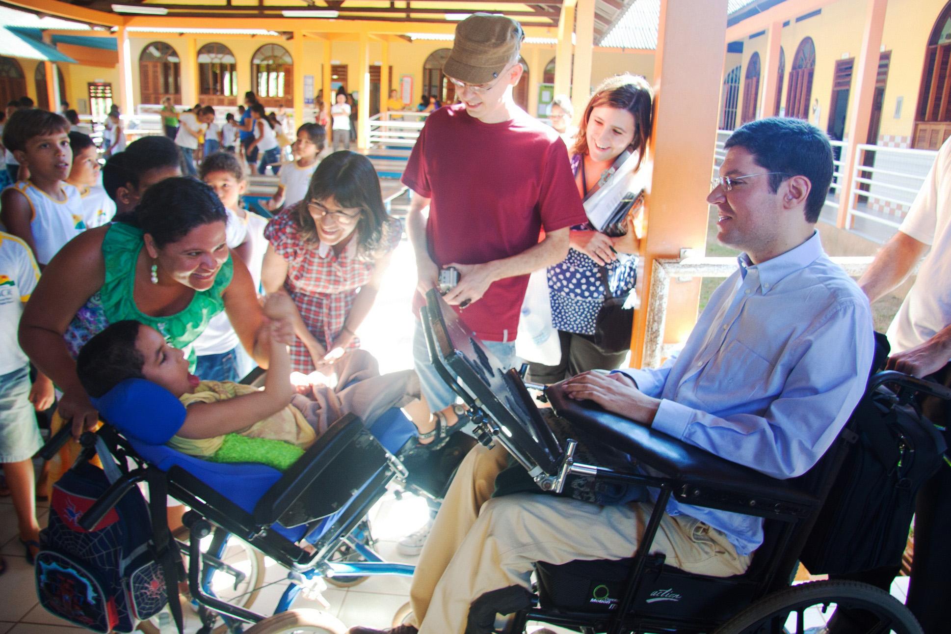 Em pátio escolar, grupo de pessoas se reúne em torno de Rodrigo e um garoto com deficiência, ambos em cadeira de rodas. A mãe do garoto, sorrindo, segura a cadeira com uma mão e, com a outra, pega a mão direita do garoto acenando para Rodrigo. Duas mulheres e um homem à volta, observam o gesto e sorriem para o garoto. Ao fundo, há crianças brincando.