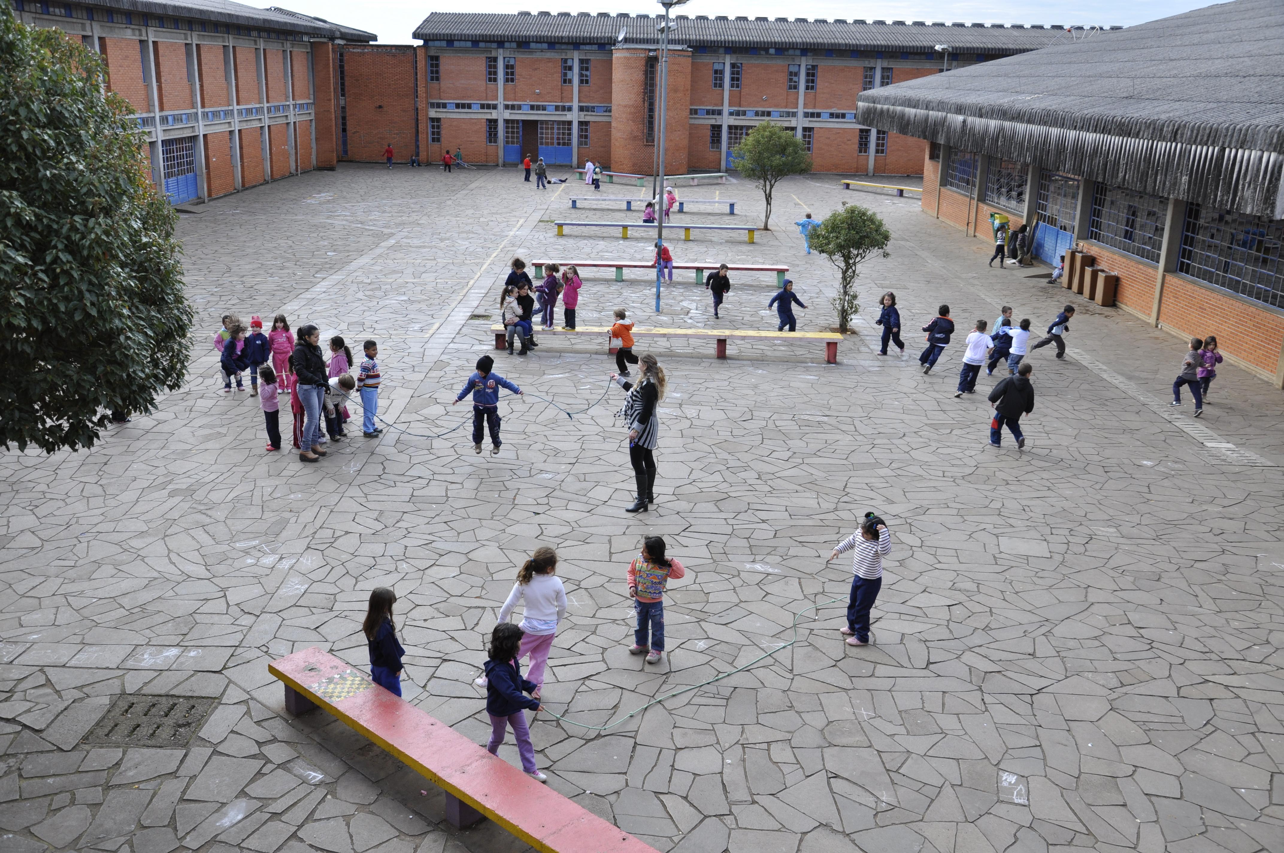 Em pátio amplo escolar, crianças brincam de pular corda e pega-pega divididas em grupos. O dia está nublado e no espaço há bancos compridos e coloridos.