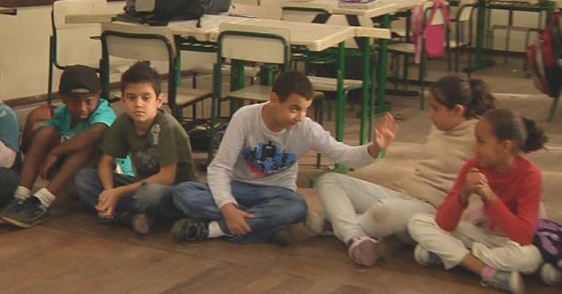 Crianças sentadas lado a lado de pernas cruzadas dentro de sala de aula. Um dos garotos acena para a colega ao seu lado. Ao fundo, mesas e cadeiras escolares.