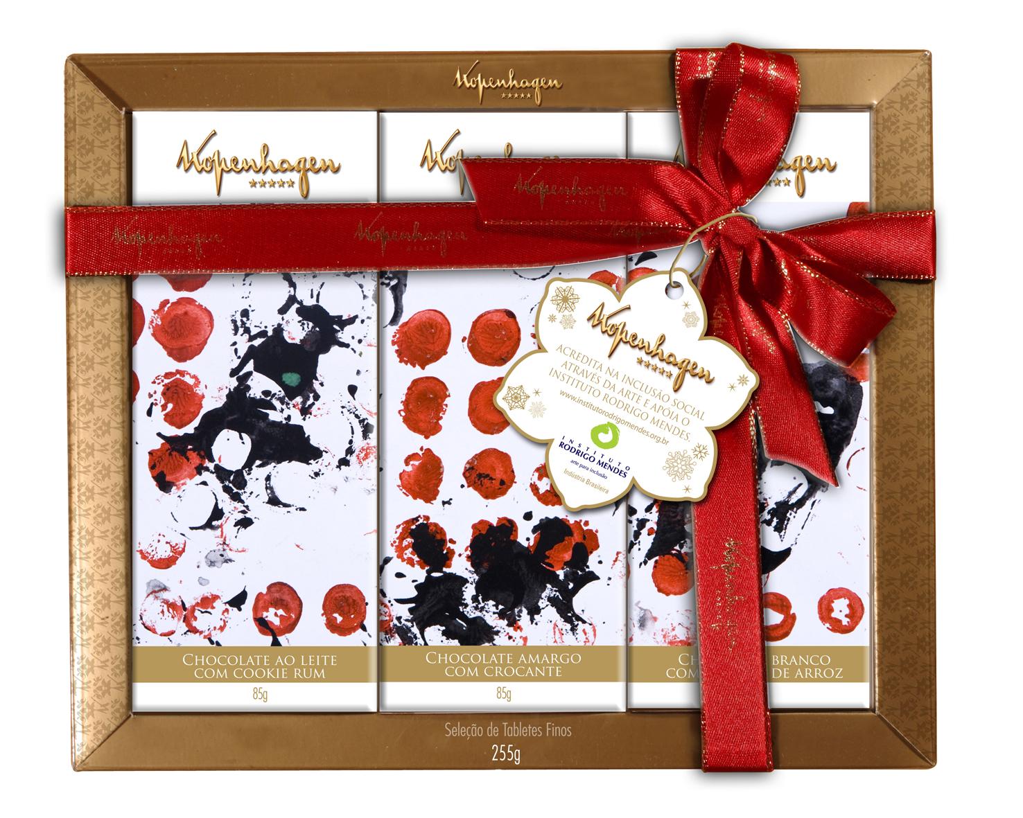 """Caixa de embalagem quadrada com borda dourada e a inscrição """"Kopenhagen"""" contendo três tabletes de chocolate em embalagens estampadas com obra de arte abstrata em preto e vermelho. A caixa está envolta por fita vermelha e um grande laço. No laço, cartão com forma de flor com o letreiro """"Kopenhagen acredita na inclusão social por meio da arte e apoia o Instituto Rodrigo Mendes""""."""