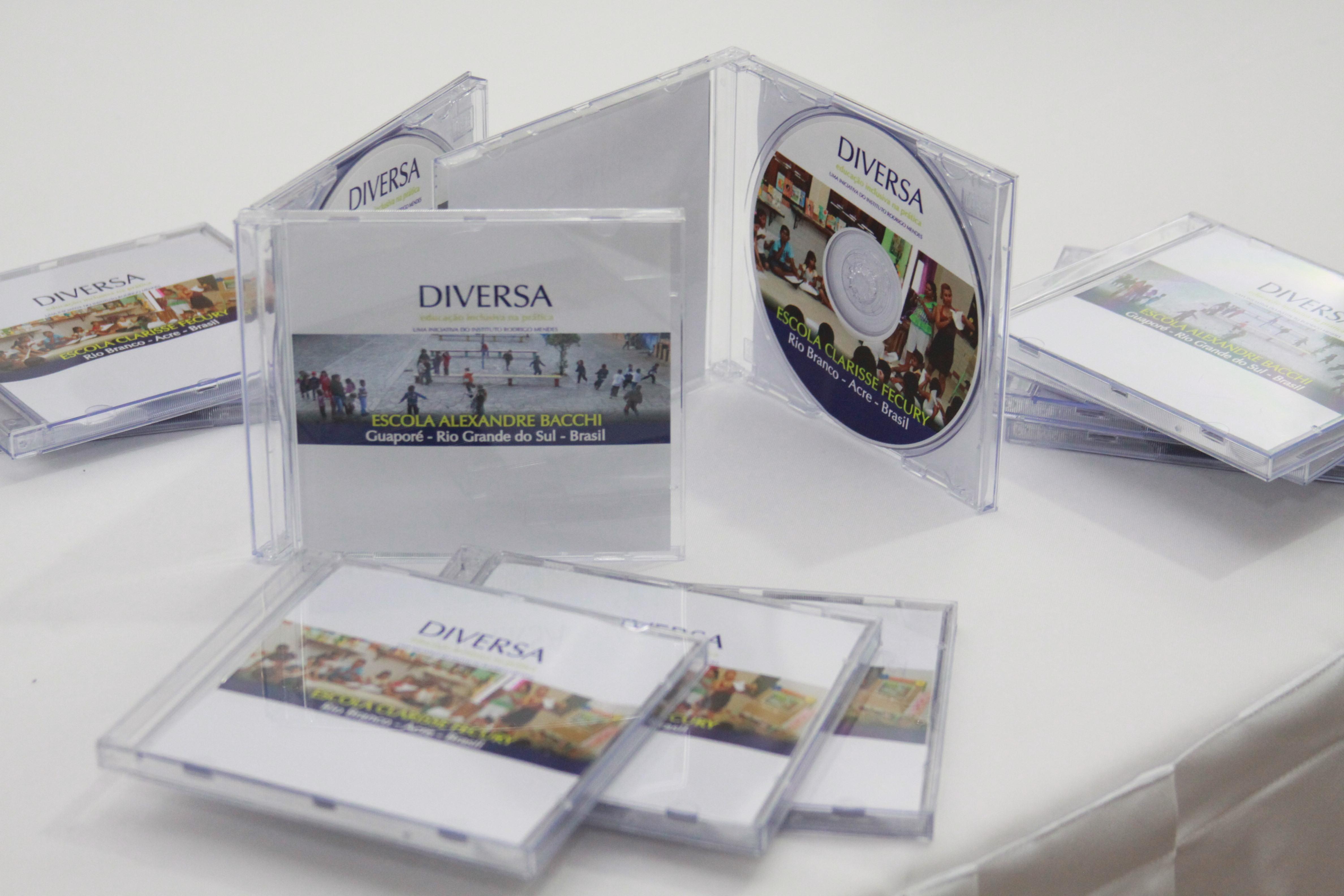 """: Capas de DVD's plásticas dispostas sobre mesa branca. Seus encartes estão estampados com fotografias. Duas delas estão em pé, abertas, apresentando o DVD que diz """"DIVERSA"""" – Escola Clarice Fecury, Rio Branco, Acre, Brasil."""
