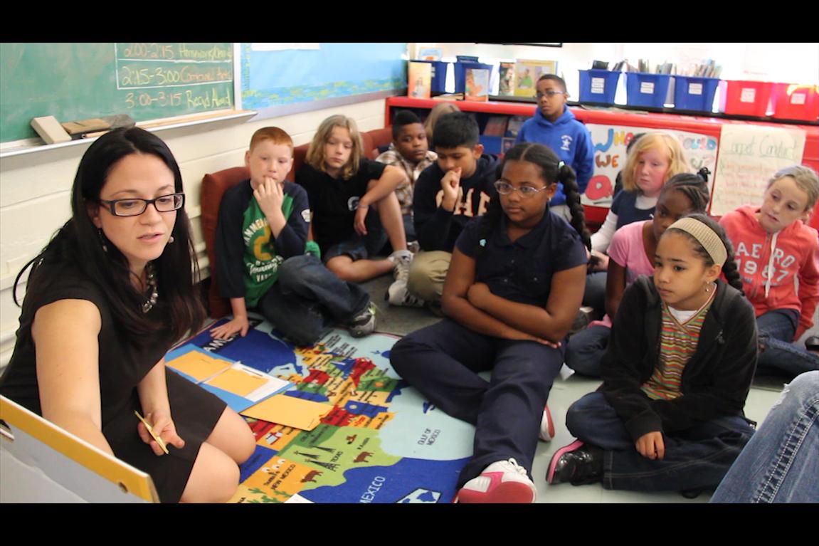 Grupo de crianças sentadas no chão da classe observam atentamente à professora que aponta para um painel.
