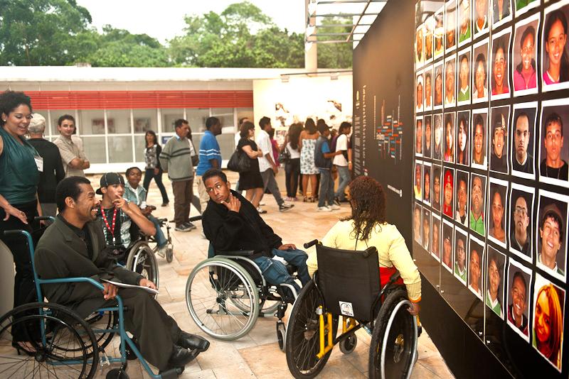 Homens e mulheres com e sem deficiência circulam em espaço aberto. Em evidência, três jovens em suas cadeiras de rodas, observam sorridentes um grande painel com fotografias de pessoas.