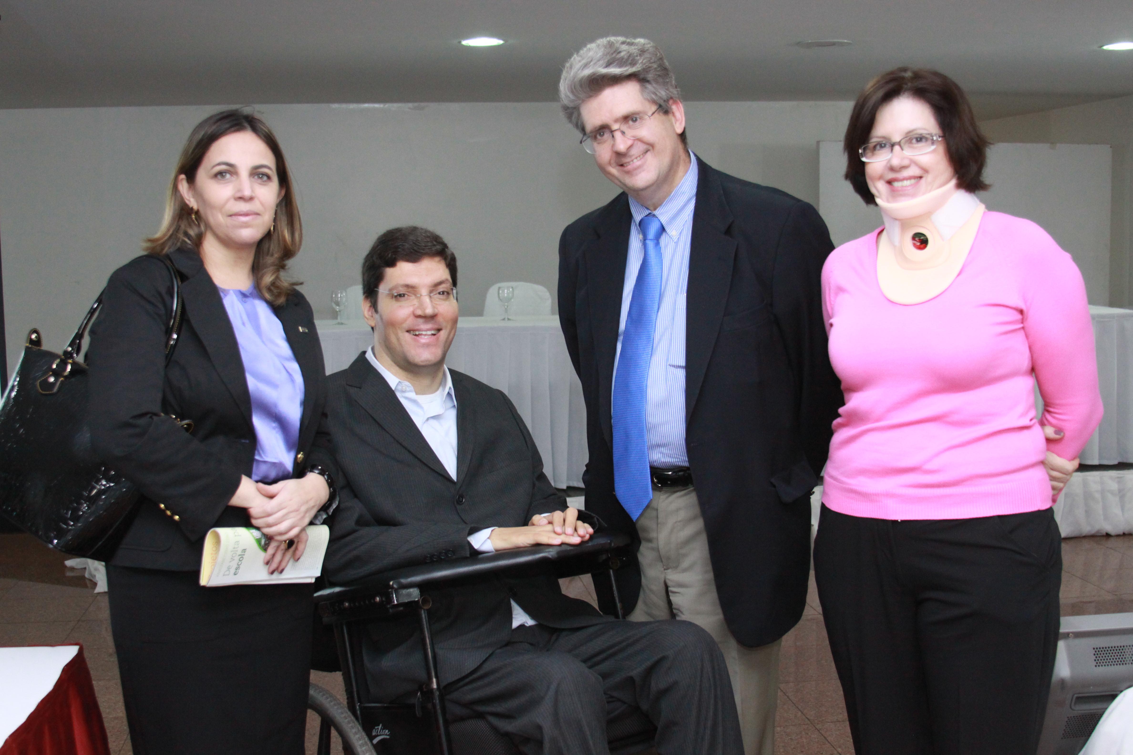 Em destaque, duas mulheres e dois homens em trajes sociais posam lado a lado sorridentes para a foto. Rodrigo está em sua cadeira de rodas e as demais pessoas estão em pé.