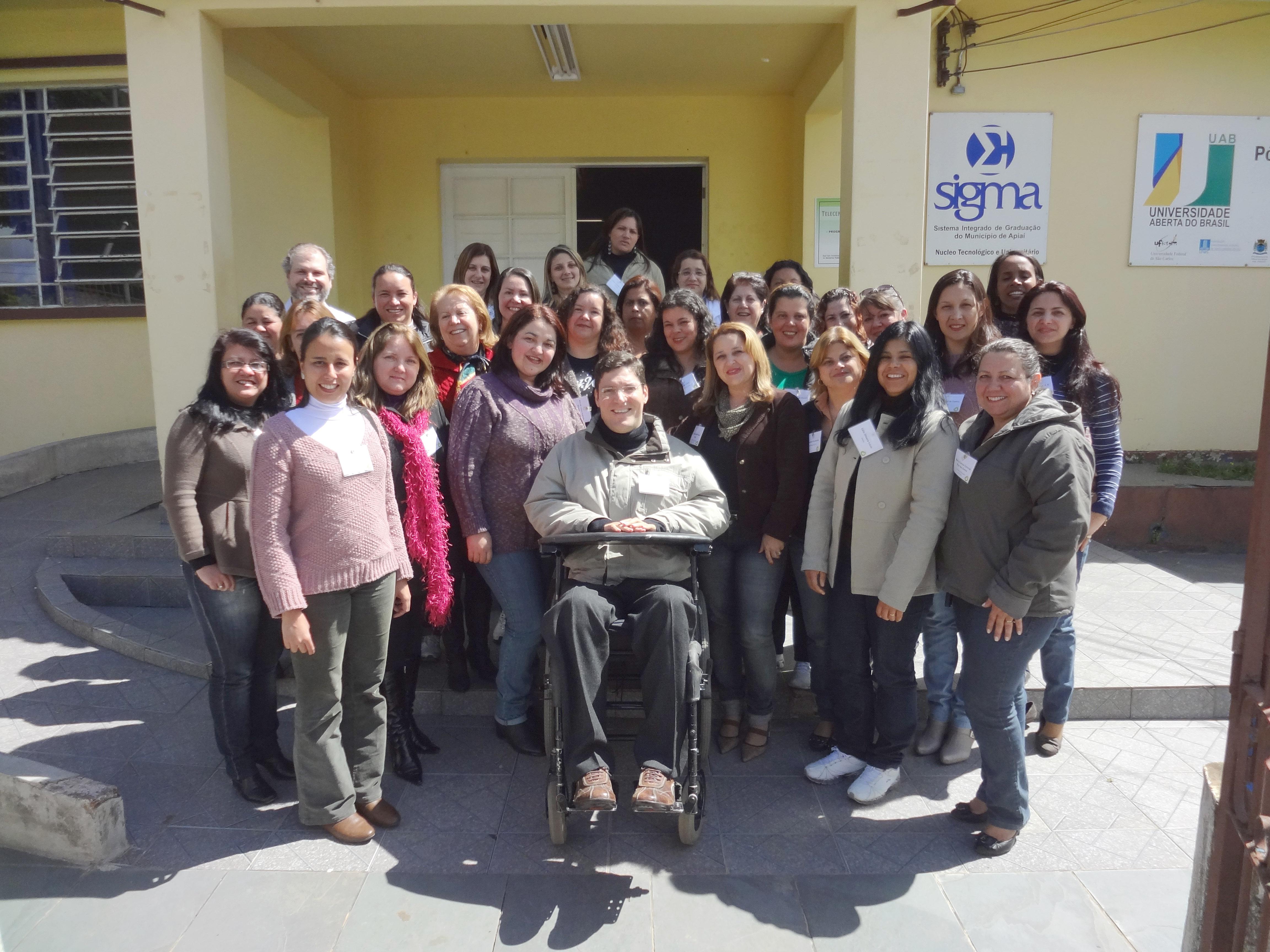 Grupo de educadoras posam sorridentes para foto em frente à universidade junto ao Rodrigo. O dia está ensolarado.