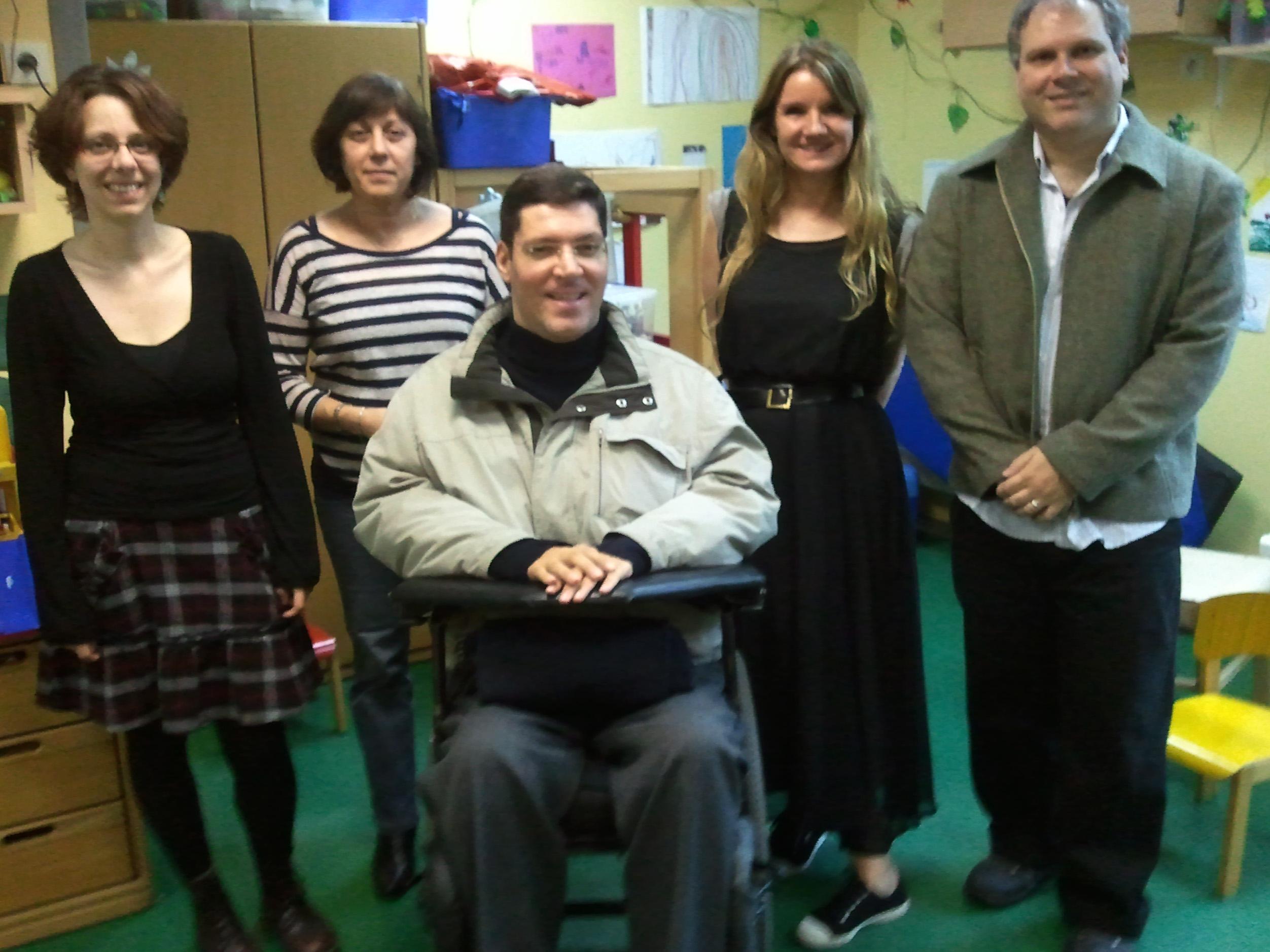 Dentro de sala de aula, três mulheres e dois homens posam de pé para a foto. Em destaque e ao centro, está Rodrigo. Ao fundo, cadeiras infantis coloridas, um armário e alguns desenhos colados na parede da sala.
